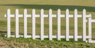 The white wooden fence with green meadow background. Stock Photo