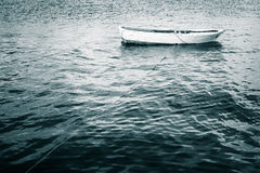 White wooden fishing boat floats on still Sea. Blue toned vintage stylized photo Royalty Free Stock Images