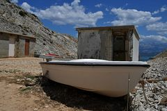 White wooden fishing boat in front of square concrete shacks. Royalty Free Stock Image