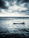 White wooden fishing boat under stormy clouds. White wooden fishing boat under dramatic stormy clouds Royalty Free Stock Photo