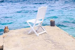 White Wooden Chair on Stone Pier against Azure Sea Stock Images