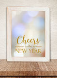 White wooden frame with Cheers to  New Year words over blur boke. H on table and cement wall bacground Royalty Free Stock Images