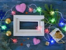White wooden frame decorated with fir branches, Christmas-tree lighting with snowflakes, felt hearts on a blue wooden textural bac royalty free stock photos