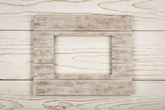 White wooden frame for picture on the wooden background. White wooden frame for picture on the white wooden background Royalty Free Stock Images