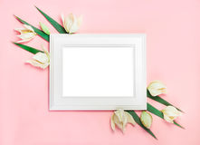 White wooden frame on pink background decorated with green leaves, blank space for a text. Top view, flat lay.  Stock Photo