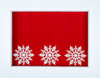White wooden frame and snowflakes over a red background Royalty Free Stock Photos