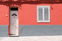 White wooden front door and white window on coral wall with gray brick. royalty free stock photo