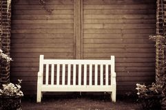 White Wooden garden bench in English garden Stock Photos