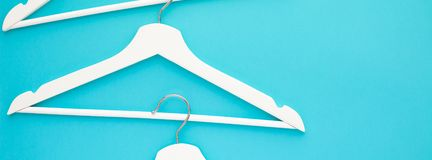 White wooden hangers on blue background royalty free stock photos