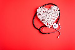 White wooden heart with black stethoscope on red paper background. Heart health concept. Top view. Flat lay. Copy space stock photography