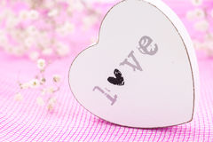 White wooden heart closeup with word Love, on pink mesh fabric and white flowers Stock Image