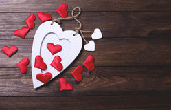 White wooden heart with many red hearts on brown wooden table. Stock Photo