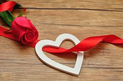 A white wooden heart with a red ribbon and red rose Royalty Free Stock Photo