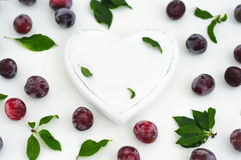 White wooden heart and ripe juicy plums. Heart and plums on a white background Royalty Free Stock Images