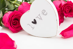 White wooden heart with word Love on it and a bouquet of red roses Royalty Free Stock Photo