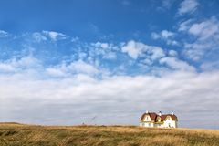 Painted house on the horizon, Cap Aux Meules. White wooden house, with red tile roof and yellow gables, on the horizon and  in a field of wild grass. Cap Aux Stock Photos