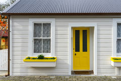 White wooden house with yellow door Stock Image