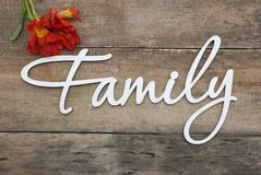 White Wooden Inscription FAMILY Letters Inscription Family Orange Red Alstromeria flowers Rustic Wooden background. Abstraction th Royalty Free Stock Images