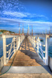 White wooden jetty walkway leading to boats and yachts in a marina Royalty Free Stock Photography