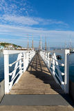 White wooden jetty walkway to marina with blue sky and clouds Royalty Free Stock Image