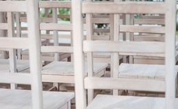 White wooden lattice. Abstract wall-paper. Wooden backs of white chairs at a wedding ceremony royalty free stock photos