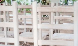 White wooden lattice. Abstract wall-paper. Wooden backs of white chairs at a wedding ceremony royalty free stock photography