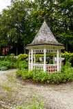White wooden gazebo in a garden or park. White wooden octagonal gazebo in a garden or park with a weedy gravel drive around it against a backdrop of leafy trees Royalty Free Stock Photo
