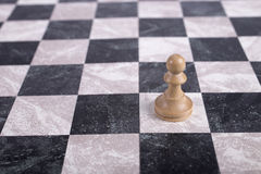 White wooden pawn on chessboard. White wooden pawn standing on chessboard Stock Photo