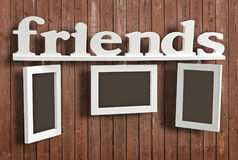 White wooden photo frame with text Friends. On wooden wall. Hanging Photo Frame consists of three frames and the word Friends Royalty Free Stock Photo