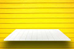 White wooden plank shelves and yellow wooden wall. Royalty Free Stock Images