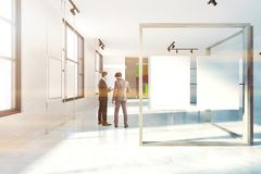 White and wooden poster gallery, front view people. White wall poster gallery with large windows, a white floor and two vertical mock up posters hanging in a Stock Photos