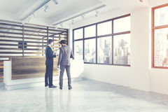White and wooden reception, side, people. Side view of a white wall and wooden office interior with a reception counter and a conference room in the background Royalty Free Stock Image