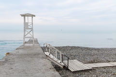 White wooden rescue tower on the breakwater. Low staircase lead Royalty Free Stock Photo