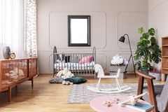 White wooden rocking horse on patterned carpet in elegant mid century baby room interior, real photo with mockup poster on the