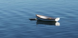 Small white wooden row boat moored in Bass Harbor MAine. A white wooden row boat with a nice reflection in the very blue waters of Bass Harbow Maine royalty free stock images