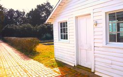 White Wooden Shingled Outbuilding in Winter With brick Pathway stock photography