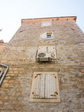 The white wooden shutters on stone wall in old Budva, Montenegro Royalty Free Stock Image