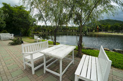 White wooden table and benches at the lakeside in nice park. Beauty of nature Royalty Free Stock Image