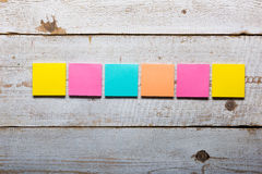 White wooden table with empty colorful sticky notes Royalty Free Stock Photos