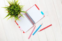White wooden table with flower, blank notepad and colorful penci Stock Photo