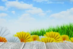 Wooden table with free space on nature background - flowers, grass and blue sky stock photo