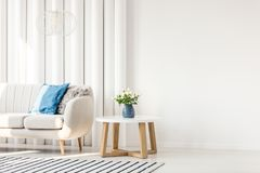 White table in living room. White wooden table next to sofa with blue cushion in empty wall living room interior stock photo