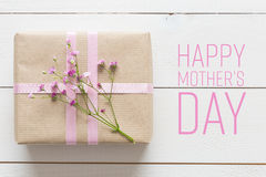 White wooden table with pink flowers and a present, mother`s day. Concept Royalty Free Stock Image