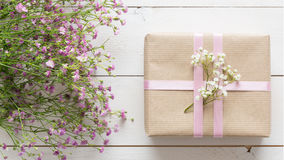 White wooden table with pink flowers and a present, mother`s day. Concept Stock Photos