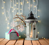 White wooden vintage lantern with burning candle christmas gifts and tree branches on wooden table. retro filtered. Stock Photo