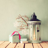White wooden vintage lantern with burning candle, christmas gifts and tree branches on wooden table. retro filtered image Royalty Free Stock Photography