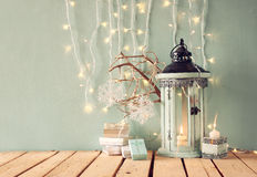 White wooden vintage lantern with burning candle, christmas gifts and tree branches on wooden table. retro filtered image Royalty Free Stock Photos