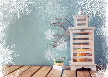 White wooden vintage lantern with burning candle, christmas gifts and tree branches on wooden table. retro filtered image. Royalty Free Stock Photo