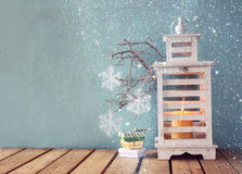 White wooden vintage lantern with burning candle christmas gifts and tree branches on wooden table. retro filtered image with glit Stock Images