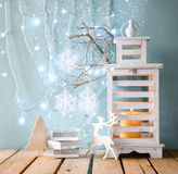 White wooden vintage lantern with burning candle christmas gifts and tree branches on wooden table. retro filtered image with glit Stock Photography